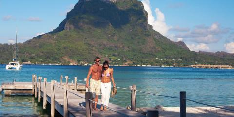 Couple walking on dock in Tahiti