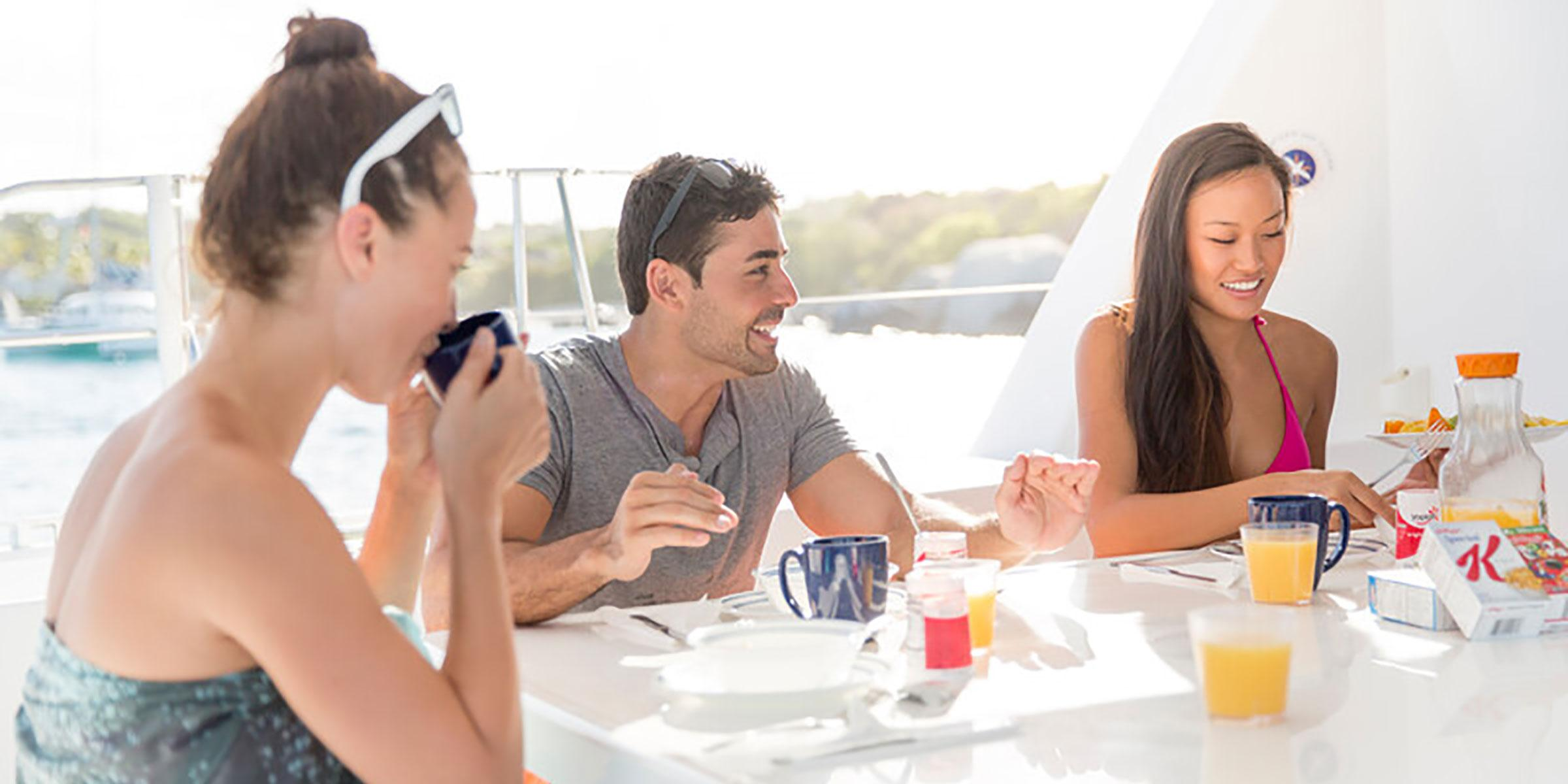 Family and friends eating breakfast aboard yacht