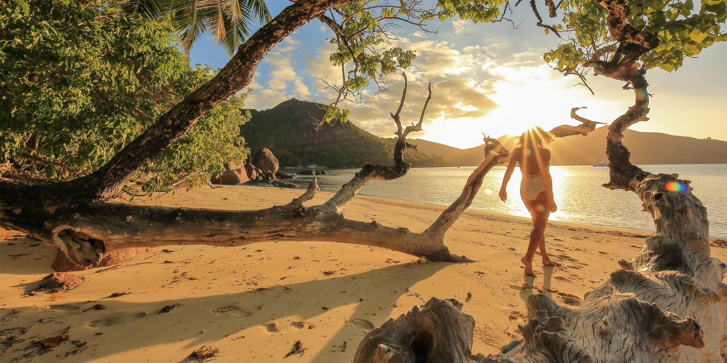 Woman walking at the beach in the Seychelles