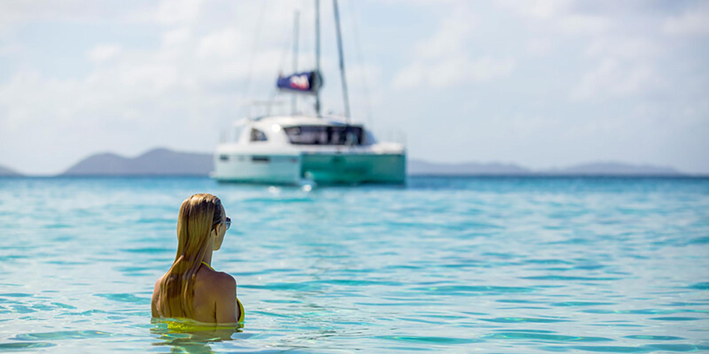 Woman swimming with sailing catamaran in view